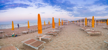 Sun loungers and umbrellas at seaside resort. Sun loungers and closed umbrellas at a seaside resort of Emilia Romagna on the Adriatic Riviera in Italy, the calm royalty free stock photos