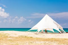 The sun loungers under the big sun shade on the idyllic beach. white tent on the beach. The sun loungers under the big sun shade on the idyllic beach royalty free stock photo