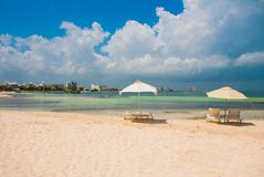 Sun loungers and umbrellas for tourists on the beach in Cancun, Mexico. Sun loungers and a white umbrellas for tourists on the beach in Cancun. Mexico royalty free stock image