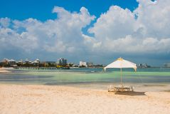 Sun loungers and umbrellas for tourists on the beach in Cancun, Mexico. Sun loungers and a white umbrellas for tourists on the beach in Cancun. Mexico stock image