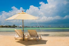 Sun loungers and umbrellas for tourists on the beach in Cancun, Mexico. Sun loungers and a white umbrellas for tourists on the beach in Cancun. Mexico royalty free stock photo