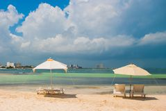 Sun loungers and umbrellas for tourists on the beach in Cancun, Mexico. Sun loungers and a white umbrellas for tourists on the beach in Cancun. Mexico royalty free stock photography