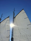 Sun Between Mainsail and Foresail of Sailboat Stock Images