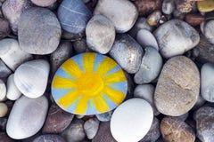 Sun malte auf Kiesel mit Steinhintergrund Stockbilder