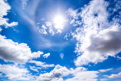 The sun in the mid day blue sky. Cloudy blue sky and the sun shining bright Stock Photography