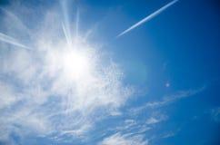 Sun mit Blendenfleck, auf Hintergrund des blauen Himmels Lizenzfreie Stockfotografie