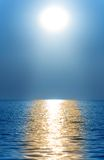 Sun or moon. Above the waves of the sea or ocean royalty free stock image