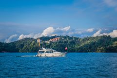 Sun moon lake. Nantou County, Taiwan - May 11, 2018: A tourist boat cruising around the Sun Moon Lake and further away on top the mountain is the Wenwumiao royalty free stock photography