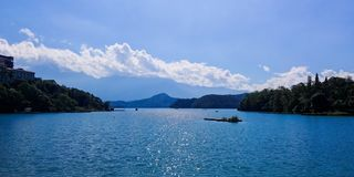 Sun Moon Lake. Picturesque photo of sun moon lake from one angle depicting the beautiful blue water, lush green vegetation on its banks and the mighty clouds royalty free stock photography