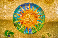 Sun mosaic at the Parc Guell, Barcelona. Ceiling with a sun mosaic at the Parc Guell designed by Antoni Gaudi, Barcelona, Spain Stock Photo
