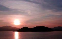 Sun, mountain, sea and water wave at sunset Stock Photos