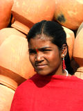 Sun n' Pots. An Indian girl in bright sunlight on a backdrop of Red Mud Pots Stock Image