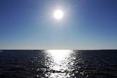 The Sun nel cielo blu ed il sole abbagliano sull'acqua fotografia stock