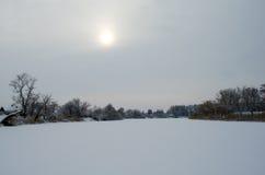 Sun no fundo de um céu cinzento do inverno e do rio congelado fotografia de stock