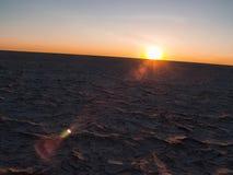 Sun no horizonte curvado sobre a crosta rachada cozida, seca de Makgadikg Imagem de Stock Royalty Free