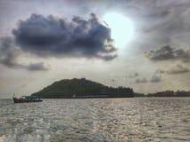 Sun, nuvem de aproximação e um barco embaixo fotografia de stock royalty free