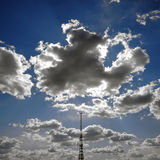 Sun obscured by clouds and antenna. On blue sky Royalty Free Stock Images