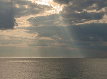Sun on the Ocean. A photograph of the sun's rays breaking through the clouds shining on the surface of the ocean Stock Image