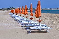 Sun orange beach umbrellas with white plastic chairs Royalty Free Stock Images
