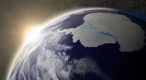 Sun over Antarctica. Sunset over Antarctica region on planet Earth viewed from space with Moon and stars in the background. Elements of this image furnished by royalty free illustration