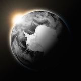 Sun over Antarctica on dark planet Earth. Isolated on black background. Highly detailed planet surface. Elements of this image furnished by NASA royalty free illustration