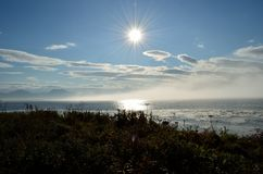 Sun over blue ocean and blue sky with heavy moving ocean mist. In autumn Stock Image