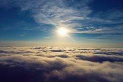 Sun over clouds with a blue sky. Fantastic landscape. stock photos