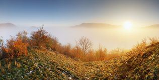 Sun over clouds mist in mountain landcape at sunrise Royalty Free Stock Images