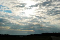 Sun over clouds and sunbeams to the earth Royalty Free Stock Photography