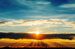 Sun over clouds in sunset time Stock Images