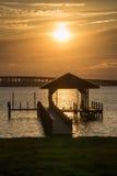Sun over dock and bridge Stock Photo