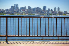 Sun over downtown Seattle with Elliott Bay and a guard rail in t royalty free stock photos