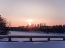 Sun over forest. Sunset in winter snow forest, view from the bridge Royalty Free Stock Images