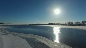 Sun over the frozen river. Aerial view HD stock video footage
