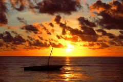 Sun over the Indian Ocean. With a traditional dhow boat in the foreground Stock Photo