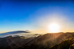 Sun over mountains on blue sky Stock Photography