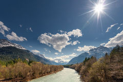 Sun over rural river between mountains Royalty Free Stock Photo