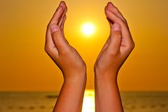 Sun over the sea in hands Stock Photography