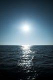 Sun over the sea horizon. Soft blue tint stock photo