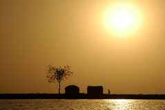 Sun over traditional West African huts Royalty Free Stock Photography