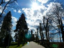 Tree alley to the water castle with great clouds and full sun royalty free stock photos