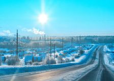 The sun over the winter forest highway in the frosty morning. The sun over the winter forest highway and the settlement Krasnogorskiy at sunrise, in the frosty stock images