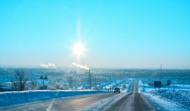 The sun over the winter forest highway in the frosty morning. The sun over the winter forest highway and the settlement Krasnogorskiy at sunrise, in the frosty royalty free stock photos