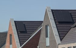 Sun panels on the roofs of new houses. Solar panels on the roof of a house against a clear blue sky Stock Image