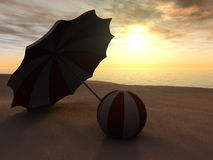 Sun parasol and beach ball on a beach at sunset. Royalty Free Stock Photography