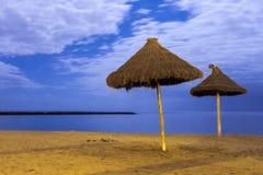 Sun parasols. Pair of sun parasols on empty beach at night Royalty Free Stock Image