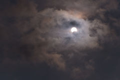 The sun during a partial solar eclipse with dark clouds . Stock Images