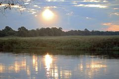 SUN PARTIALLY HIDDEN BEHIND CLOUDS REFLECTING ON WATER AT SUNDOWN royalty free stock image