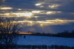 Sun peaking through clouds on a arctic cold day royalty free stock image