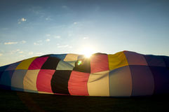 Sun peaking over the inflating envelope of a hot air balloon Royalty Free Stock Photography